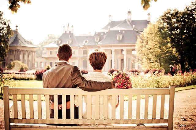 Liebespaar auf der Bank vor einem Gebäude